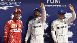 Hamilton celebra la 'pole' escoltado por Vettel y Bottas.