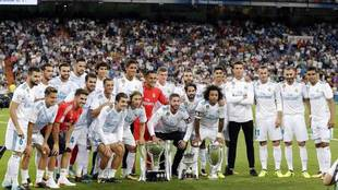 Los jugadores blancos posan con la Liga y con la Supercopa de Europa y...