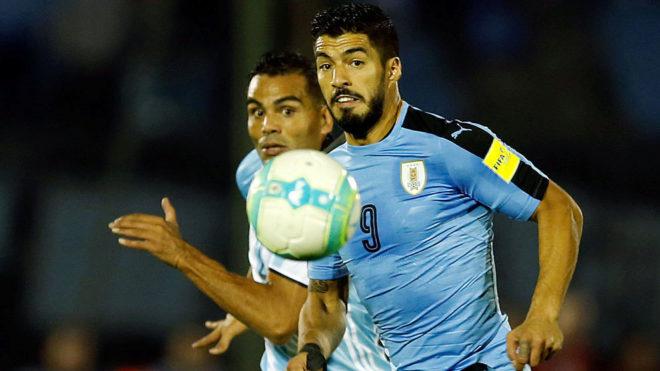 Mercado y Suárez observan el balón.