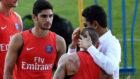 Guedes observa c�mo el presidente del PSG Nasser Al-Khela�fi abraza...