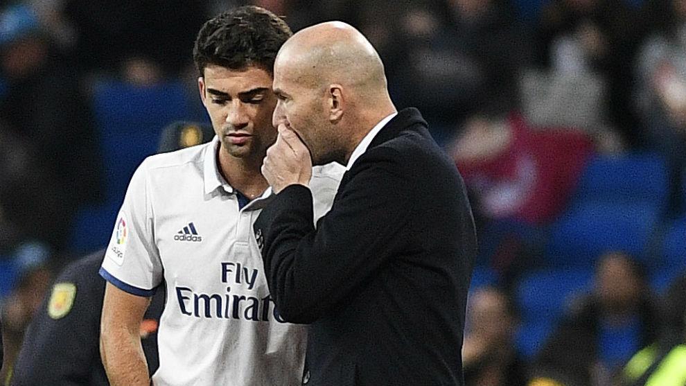 Zidane charla con su hijo, Enzo, antes de darle entrada en un partido.
