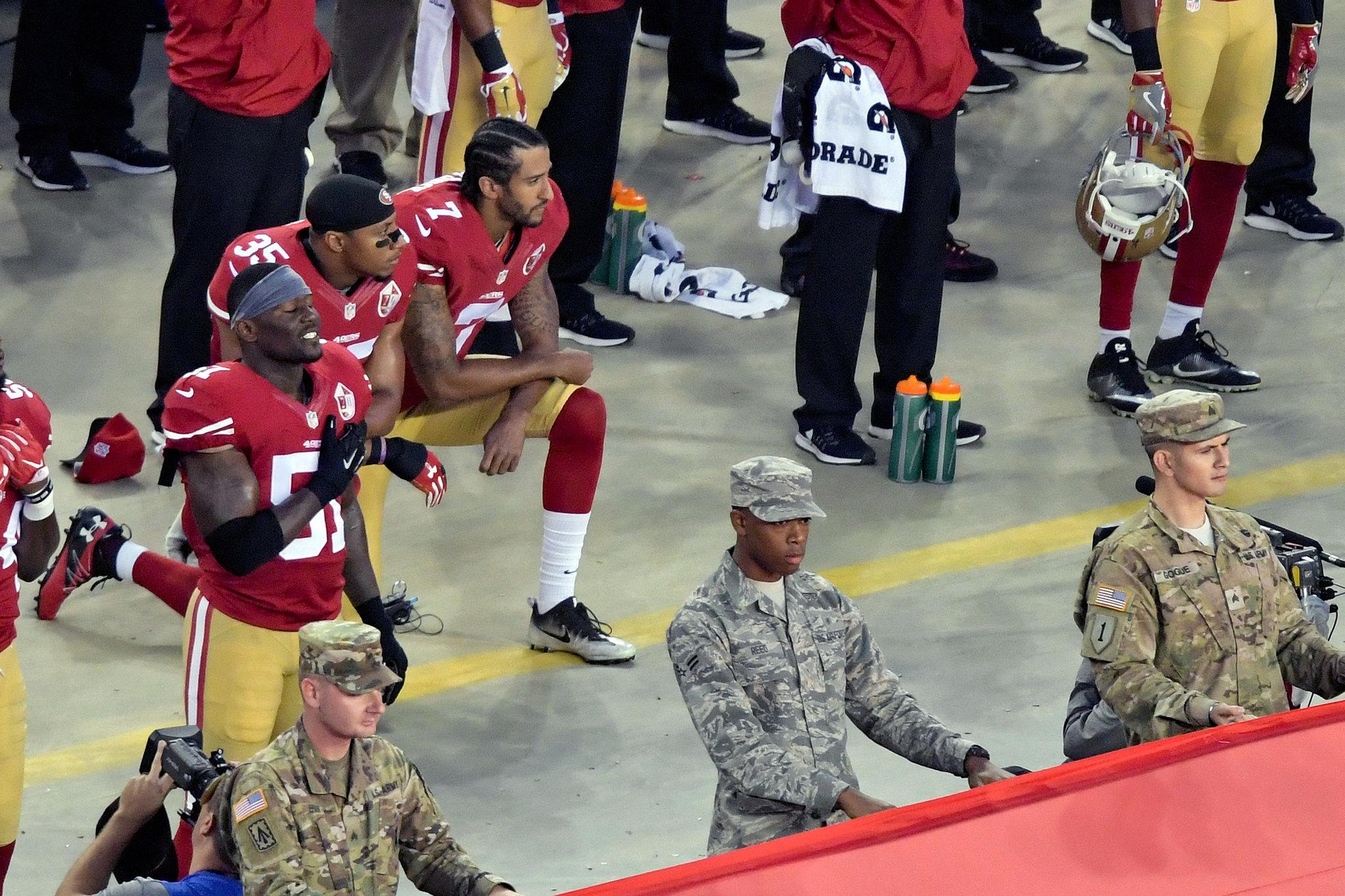 Colin Kaepernick y dos jugadores de los 49ers se hincan durante el...