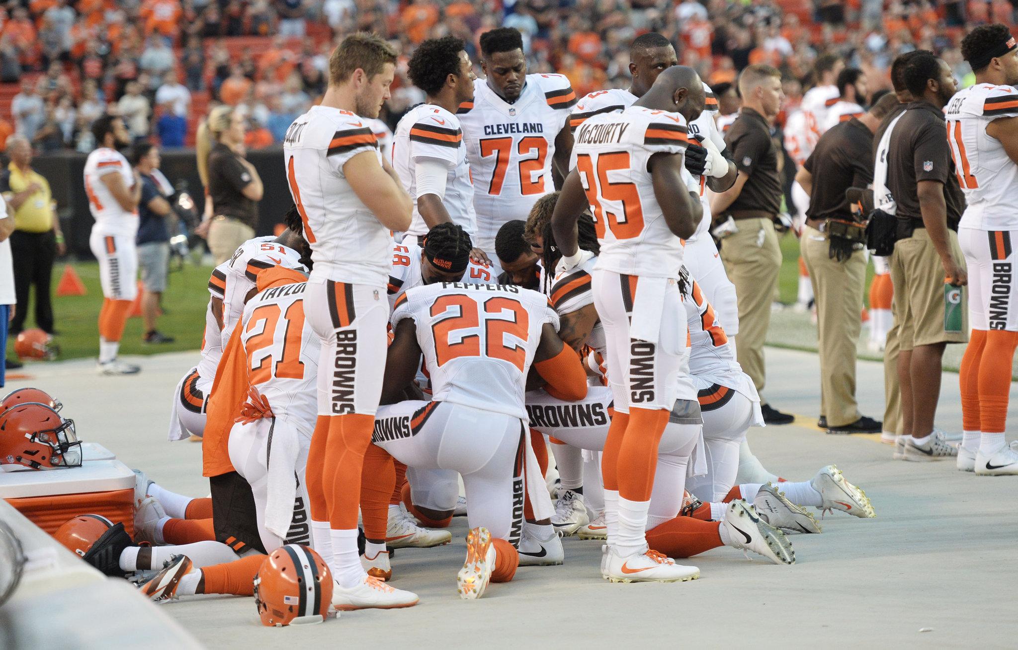Jugadores de los Browns de Cleveland se hincan durante el himno en un...