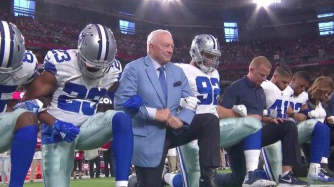 Jerry Jones se arrodilla antes del himno.