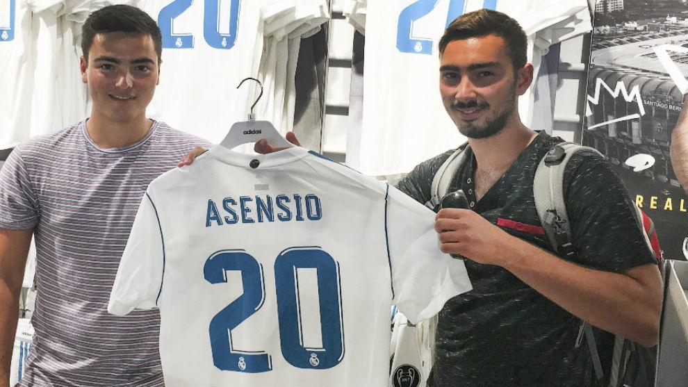 Dos aficionados en la tienda del Bernabéu con la camiseta de Asensio.