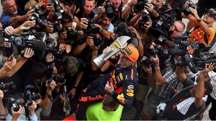Verstappen, con el trofeo, rodeado de fotógrafos.
