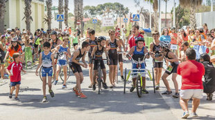 Emocionante momento de un triatlón en el que varios chicos animan a...