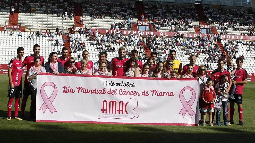 Los jugadores del 'Alba' lucen de rosa junto a integrantes de la AMAC