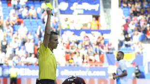 El árbitro Jaime Latre muestra tarjeta amarilla.