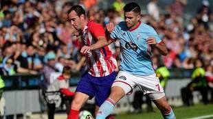 Godín disputa un balón con Maxi Gómez.