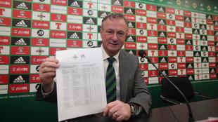 Michael O'Neill (48) muestra la lista de convocados que ha...