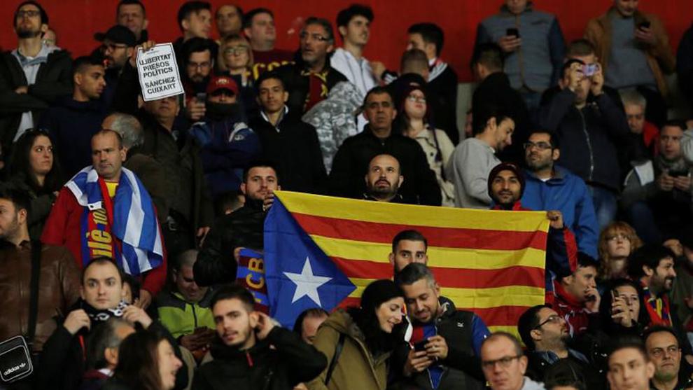 Aficionados sostienen la bandera de Cataluña mientras otro muestra...