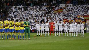Los dos equipos guardan el minuto de silencio.