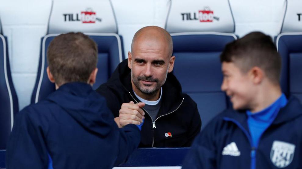 Pep Guardiola saluda a un chico en la previa del partido entre el West...
