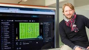 Sven Mislintat posa con una pantalla con alineaciones al fondo.