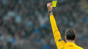 Olegario Benquerença muestra una amarilla durante un partido de...