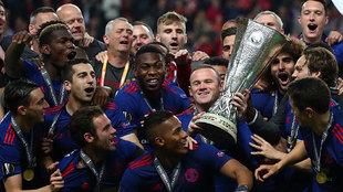 Los futbolistas del Manchester United levantan el trofeo de la última...