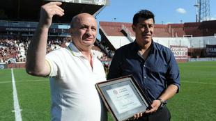 El presidente de Lanús, Nicolás Russo, entrega a Jorge Almirón una...