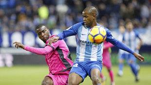 Rolan, con la camiseta del Málaga, disputa un balón con un jugador...