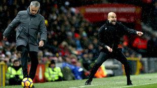 Guardiola da indicaciones mientras Mourinho controla el balón.