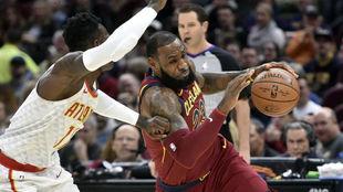LeBron James trata de superar la defensa de Dennis Schroder