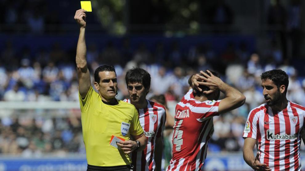 El colegiado Juan Martínez Munuera enseña la tarjeta amarilla a...