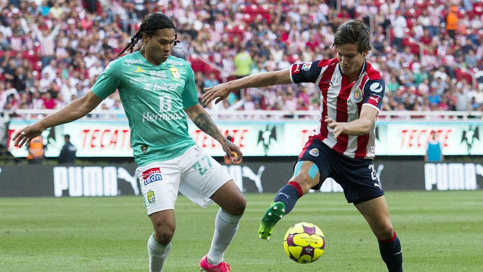 Carlos Peña y Carlos Fierro disputan un balón en un León vs Chivas.