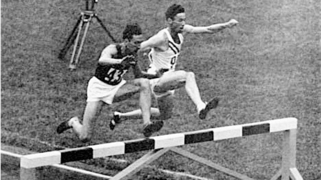 Horace Ashenfelter (de blanco) salta un obstáculo junto a su rival el...