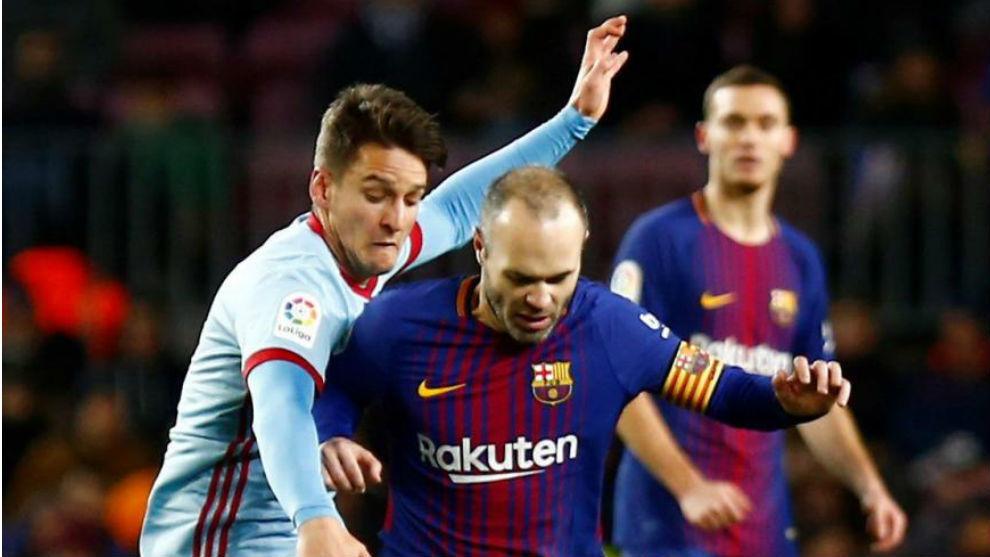 Andrés Iniesta pugna por un balón.