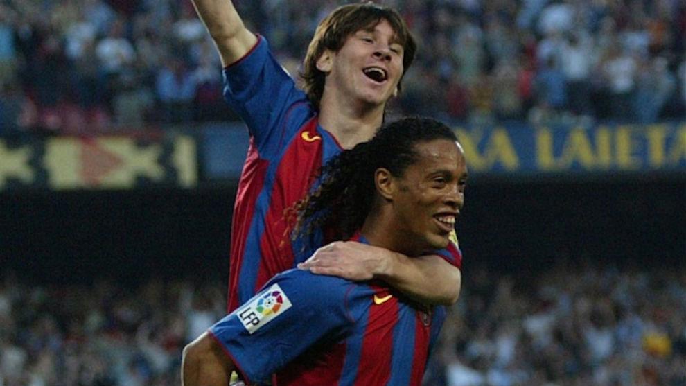 Ronaldinho con Messi a cuestas tras darle su primer gol con el Barça.