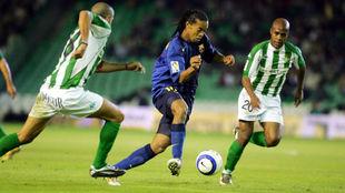 Ronaldinho, seguido por Assunçao en el Villamarín, en la 2004-05.