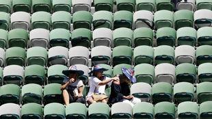 Tres aficionadas intentan protegerse del sol