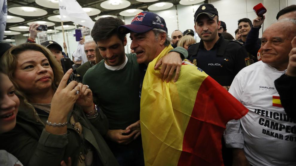 Sainz, con la bandera española, abrazado por su hijo.