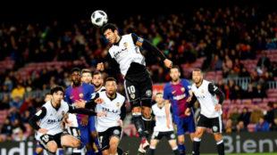 Parejo salta para despejar un balón en el Barça-Valencia.
