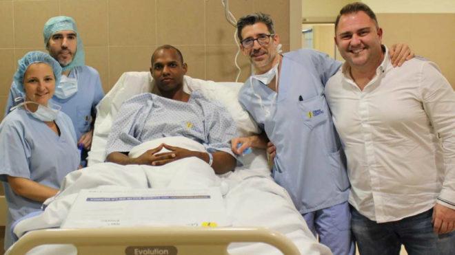 El atleta junto a los médicos que le han intervenido y su...