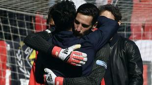 Rico (24) es felicitado por Silva, preparador de porteros del Sevilla.