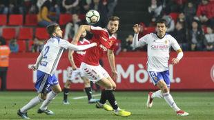 Zapater y Benito tratan de quitarle el balón a Manu Barreiro.