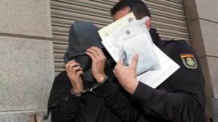 Uno de los detenidos en Murcia este lunes junto a un policía.