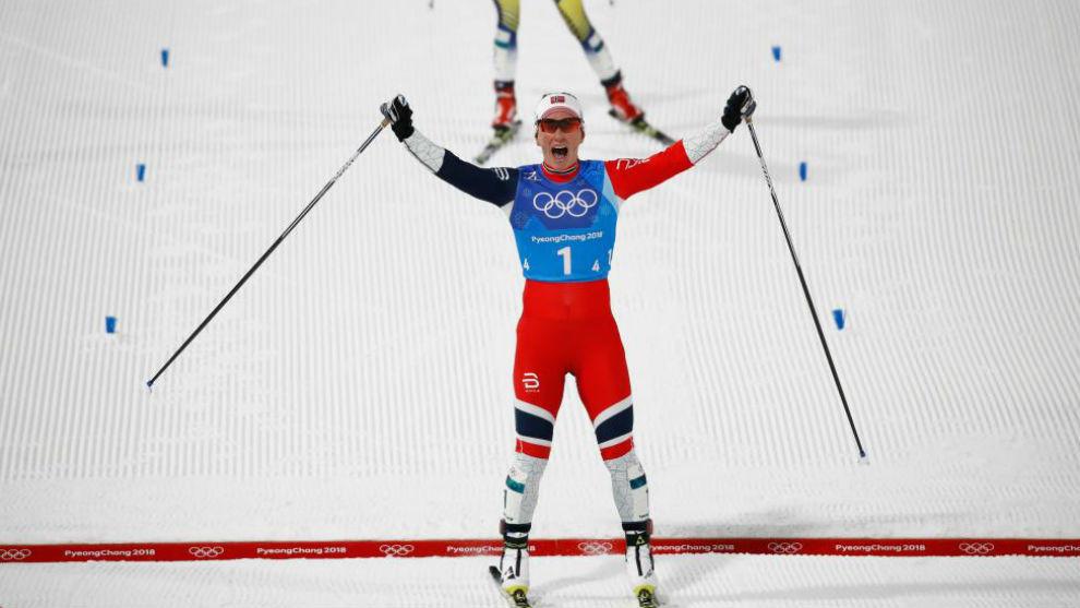 Marit Björgen levanta las manos al cruzar la línea de meta en...