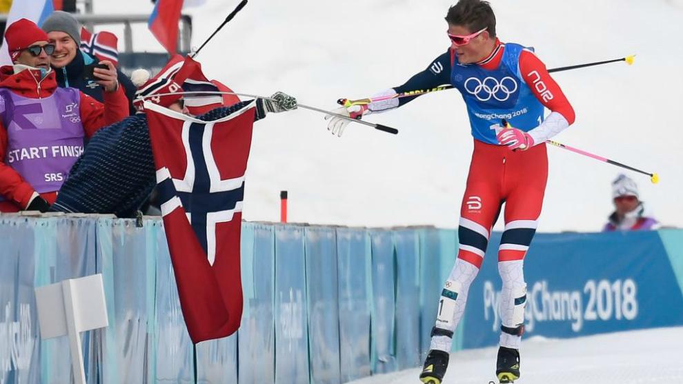 Johannes Hoesflot Klaebo recoge la bandera noruega tras entrar en...