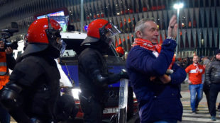 Un aficionado del Spartak posando entre los cuerpos de segurodad y San...