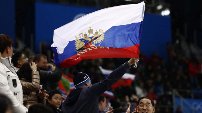Un seguidor ruso en las gradas del hockey ondeando la bandera de su...