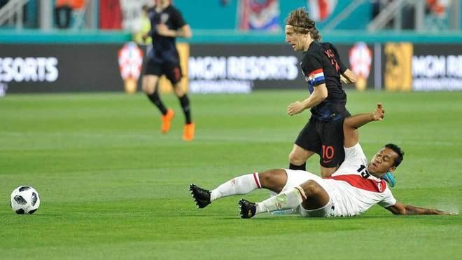 Modric disputa el balón con Renato Tapia.