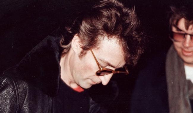 John Lennon, 40 ans.  L'homme qui a abattu le fondateur des Beatles apparaît à droite de la photo pour demander un autographe.  L'image est prise à peine quatre heures avant sa mort.