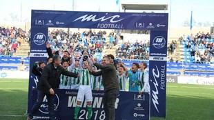 Los jugadores del Betis reciben el trofeo de campeón de manos de...