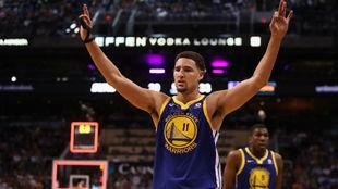 Klay Thompson levanta los brazos celebrando su prodigiosa actuación...