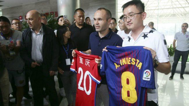 Iniesta posa con una camiseta del Chongqing Dangdai Lifan junto a...