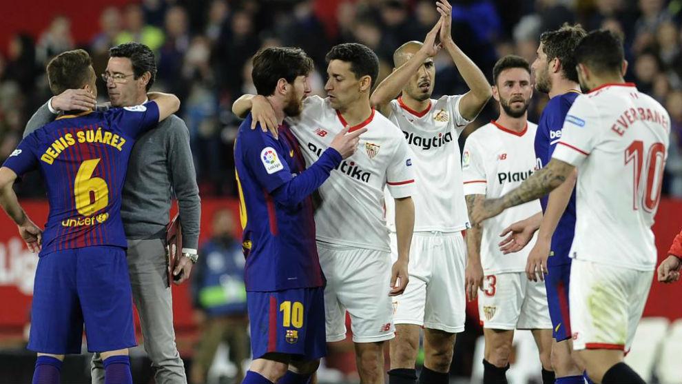 Jugadores del Sevilla y del Barcelona se saludan tras el último...