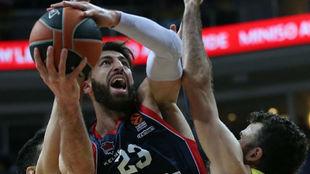 Tornike Shengelia intenta levantar el balón ante la defensa de Ahmet...