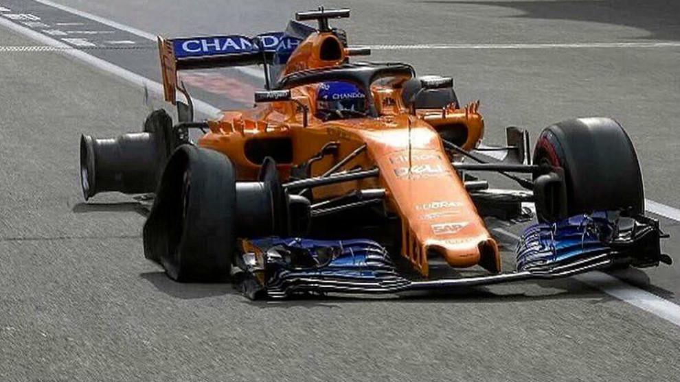 Fernando Alonso, con las dos ruedas derechas destrozadas llegando a...